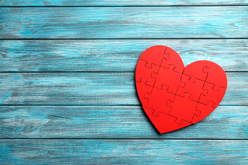 Red puzzle heart on blue wooden background