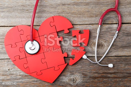 istock Red puzzle heart with stethoscope on grey wooden background 472002142