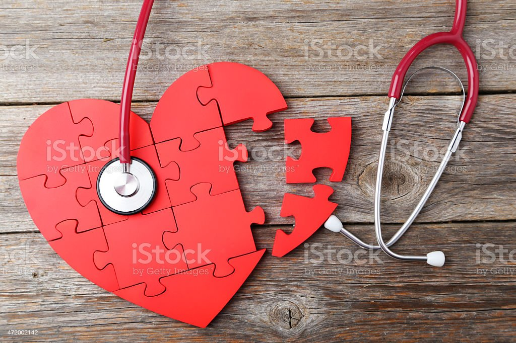 Red puzzle heart with stethoscope on grey wooden background stock photo
