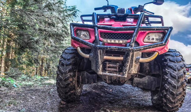 red quad bike in the forest, close-up red quad bike in the forest, close-up, front view quadbike stock pictures, royalty-free photos & images