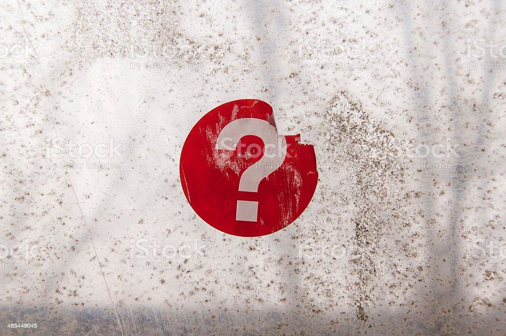 Red question mark sticker on an old weathered window stock photo