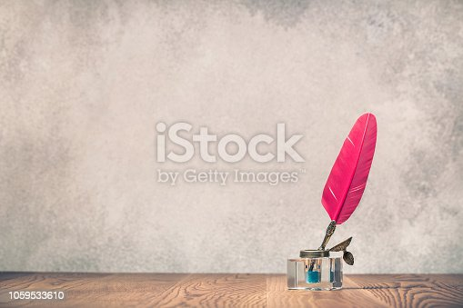 istock Red quill ink pen with inkwell on wooden desk front concrete wall background. Vintage old style filtered photography 1059533610