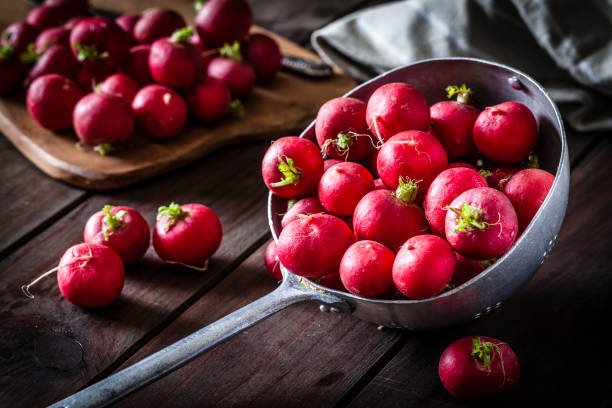 Red radish in an old metal colander stock photo