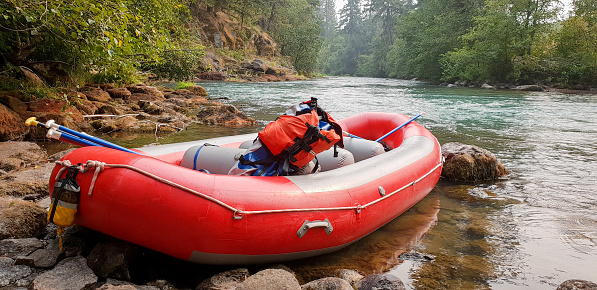 Red raft on edge of beautiful river with backpack and ores resting inside