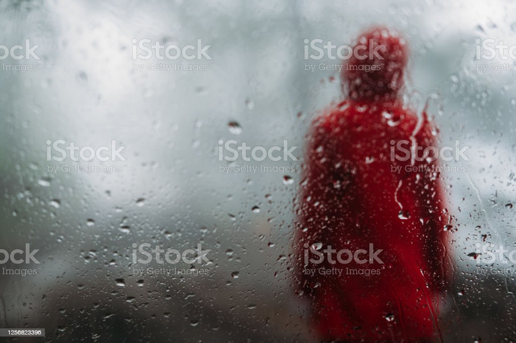 Red raincoat girl Mountain Stolovi, Serbia. A girl with a red jacket standing on the dirt road in the misty forest. View from the windshield full of raindrops. Active Lifestyle Stock Photo