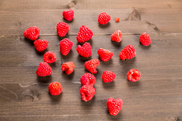 Red raspberries on a wooden background stock photo