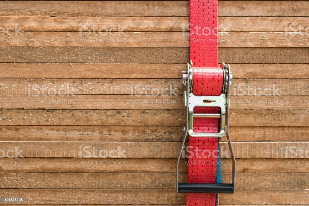 red ratchet strap fixing wood boards / wooden planks stock photo