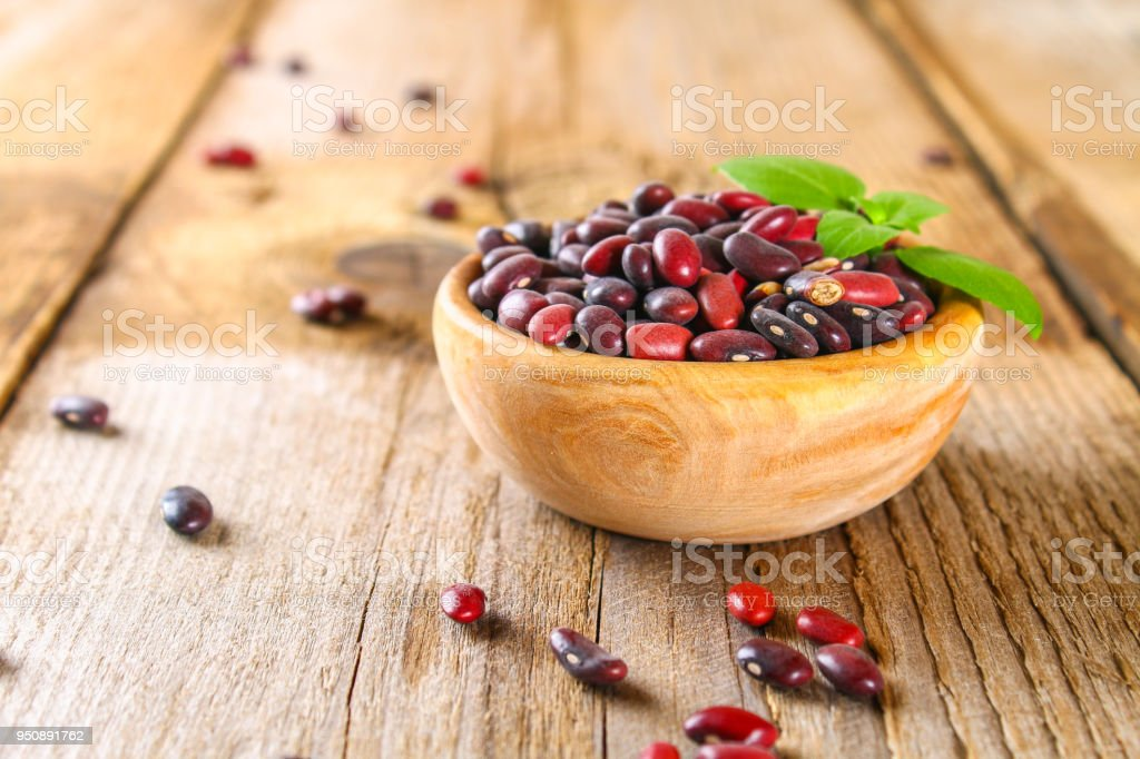 Red raw beans with greens on a wooden table. stock photo