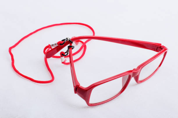 Red reading glasses with a red neck strap on a white surface stock photo