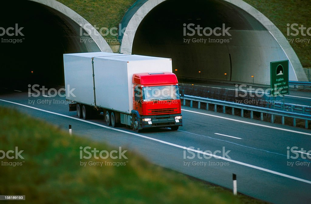 Red refrigerator truck coming out of the motorway tunnel royalty-free stock photo