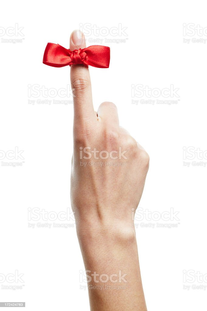 A red reminder bow tied on an index finger royalty-free stock photo