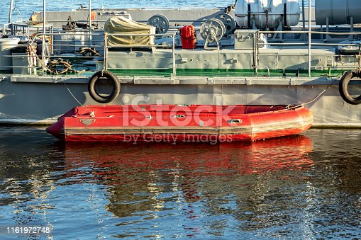 red  rescue inflatable boat at the side of a warship