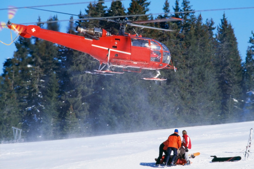 red rescue helicopter arriving after a ski accident