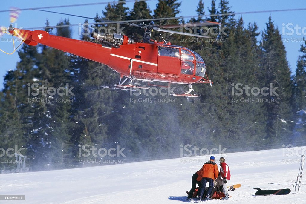 red rescue helicopter arriving after a ski accident stock photo