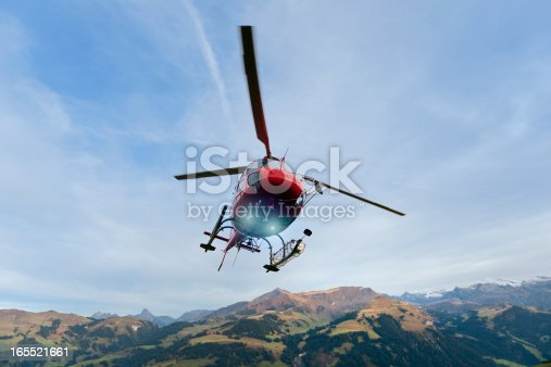 red rescue helicopter landing on mountain in Bernese Oberland Switzerland, Lenklypse 2012