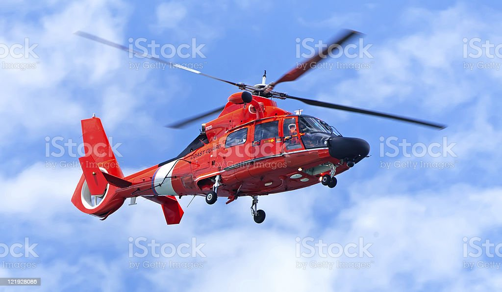 Red rescue helicopter moving in blue sky stock photo