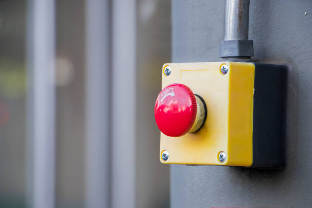 Red Reset button on the wall. red emergency stop switch button in a factory building. stock photo