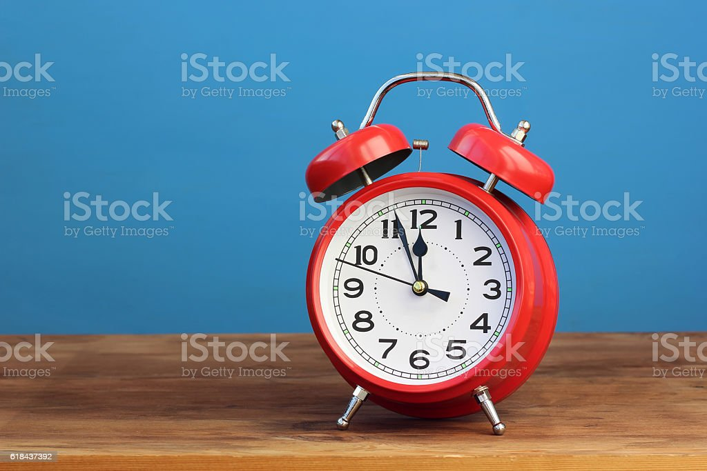 Red retro alarm clock at twelve o'clock. stock photo