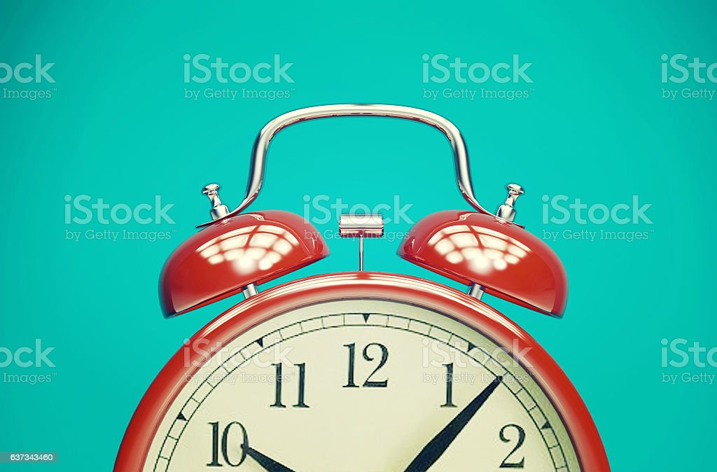 Red retro alarm clock on blue background with vintage filter​​​ foto