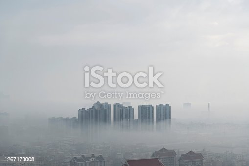 Red retro houses and skyscraper in foggy day.