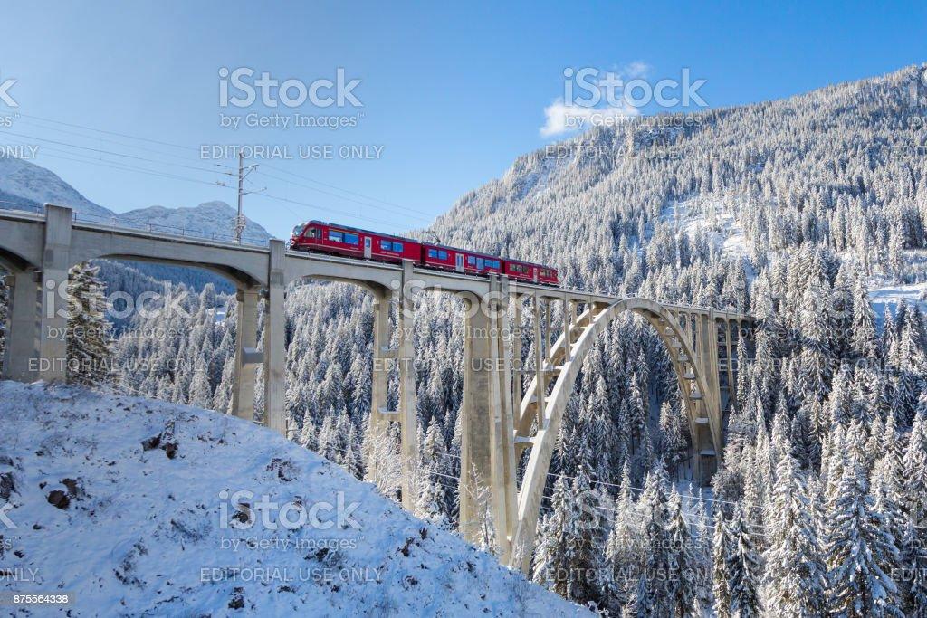 red Rhaetian railway train on viaduct Langwies, sunshine, winter, snow, blue sky stock photo