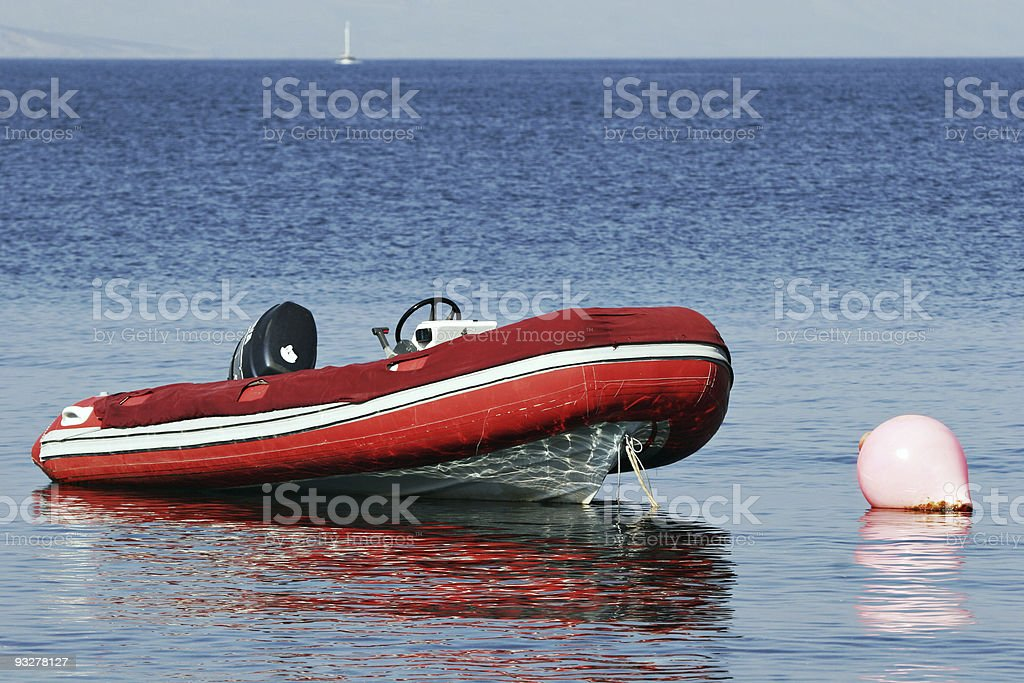 red RIB, rigid inflatable boat moored at buoy stock photo