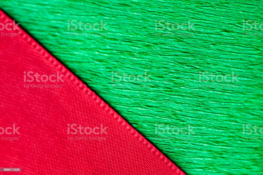Red ribbon and green wrapping paper texture close up. stock photo