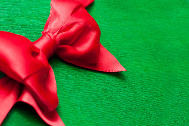Red ribbon bow on green wrapping paper backround with copy space stock photo