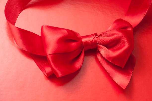 Red ribbon bow on red backround. stock photo