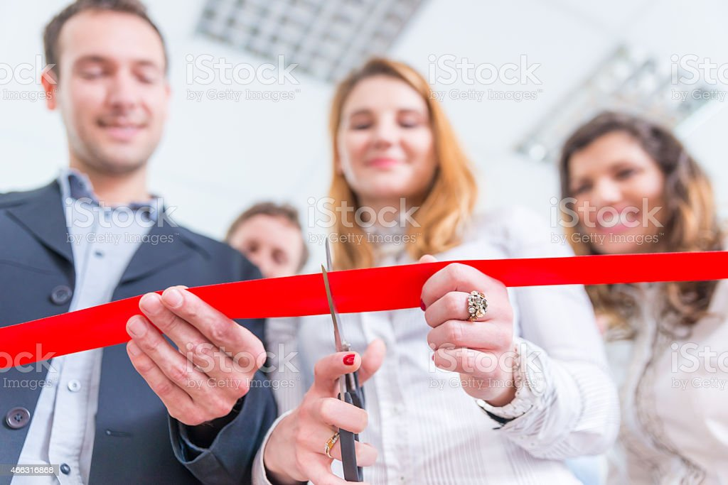 Red ribbon cutting ceremony from low angle stock photo