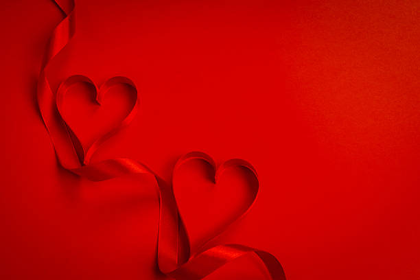 Red ribbon making the shape of heart on red background – Foto