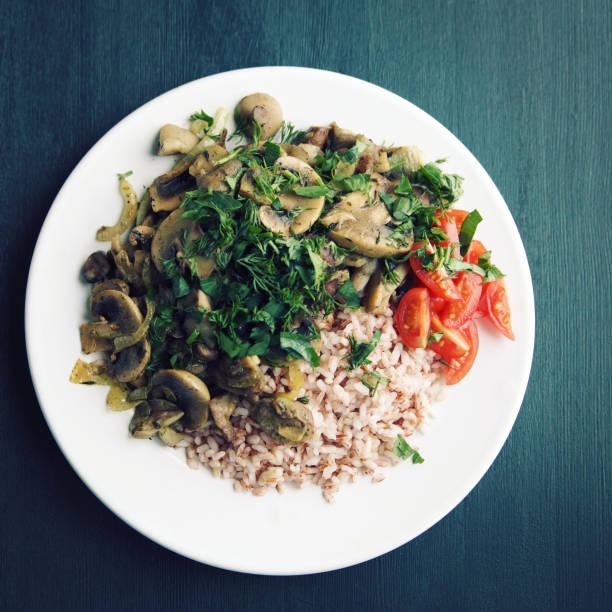 Roter Reis mit Pilzen und Tomaten. Veganes Gericht. – Foto