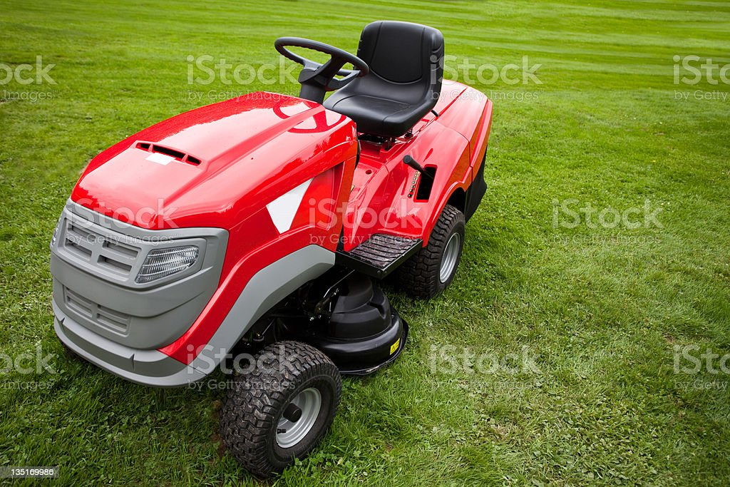 Red riding mower parked on the grass stock photo
