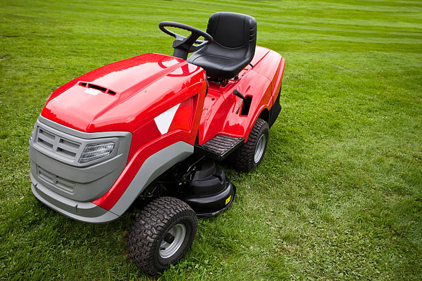 red riding mower parked on the grass - riding lawn mower stock photos and pictures