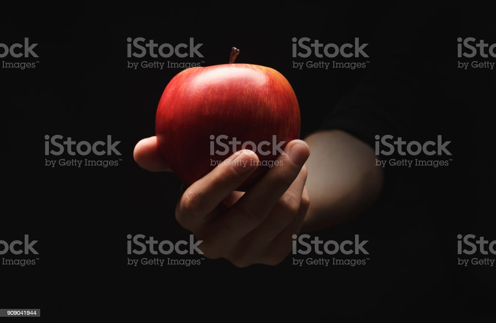 Red ripe apple on male hand, isolated on black stock photo
