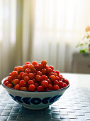 Red ripe cherries on ceramic bowl on wooden table