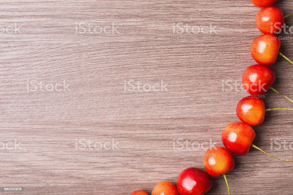 Red ripe cherry lies in a row on a wooden background. Place for text for your design. royalty-free stock photo