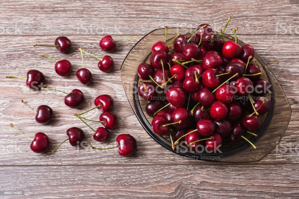 Red ripe juicy sweet cherry lies in a transparent plate on a vintage wooden background. Sweet summer berries. royalty-free stock photo