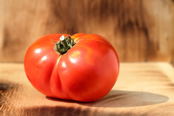 Cтоковое фото Red ripe large tomato on wooden background.