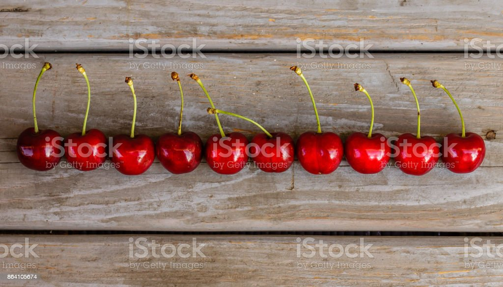 Red ripe organic cherries in row on a wooden background royalty-free stock photo