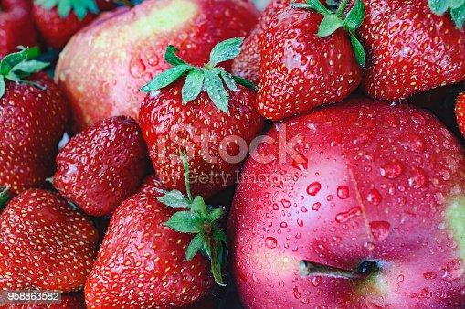 Close-up photo of summer fresh fruits with strawberry in the focus and a lot of water drops on it.