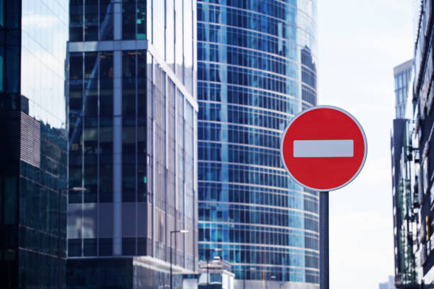 Red road stop sign or brick on city skyscrapers business center blurred background close up, entrance prohibition, restriction or no way symbol, no entry allowed or forbidden traffic sign, copy space Red road stop sign or brick on city skyscrapers business center blurred background close up, entrance prohibition, restriction or no way symbol, no entry allowed or forbidden traffic sign, copy space sanctions stock pictures, royalty-free photos & images