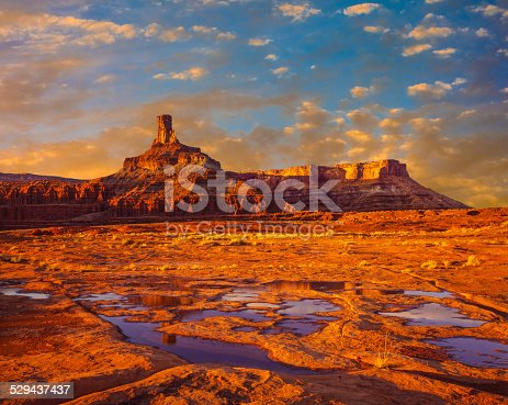 Looking at Deadhorse Point State Park near Canyonlands National Park with red rock butte at sunset, Utah, right after a big storm. Water fills the plateau in little ponds.