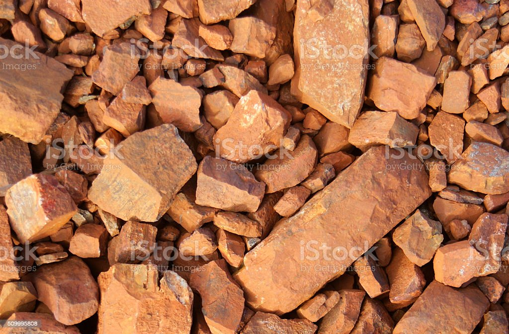 Red rocks on the ground at an iron ore mine. stock photo