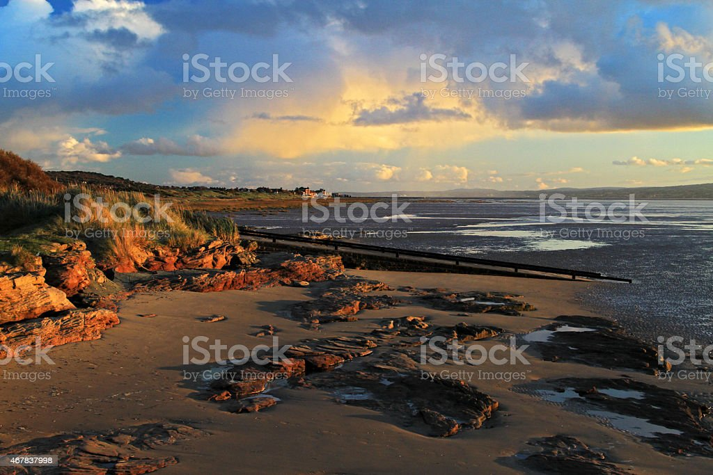 Red Rocks Late evening sunshine bathes the sanstone rocks and coastline set against a turbulent sky 2015 Stock Photo