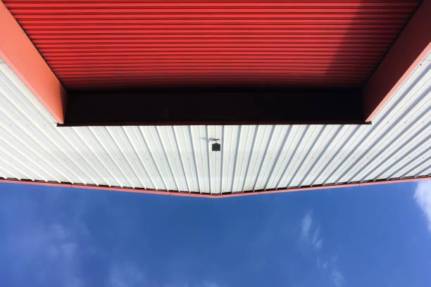 rote rolltür an der außenseite eines wellblechgebäudes - schuppen türen stock-fotos und bilder