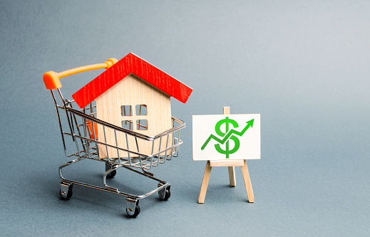 831745600 istock photo A red roof house in a trading cart and green arrow up on a stand. Increasing the cost and liquidity of real estate. Attractive investing. rising prices or renting. The boom in the property market 1161032479