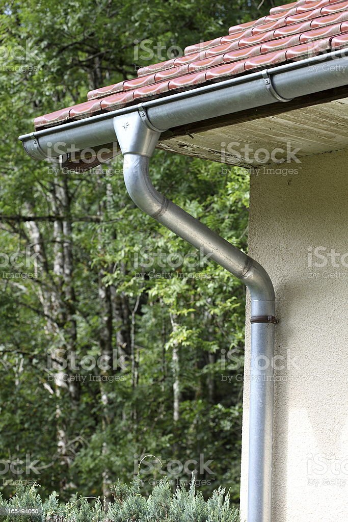 Red roof with aluminum gutter and drain pipe royalty-free stock photo