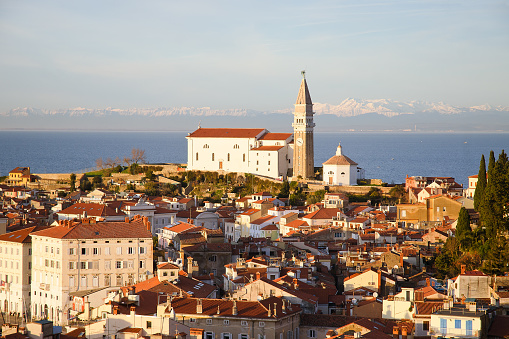 Red roofs of the historical center of old town Piran with main church against the sunset sky and Adriatic sea. Aerial view, Slovenia