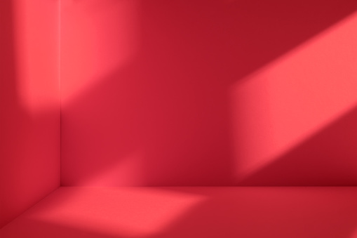 Empty corner of red room with deep window shadow. Minimalistic space concept